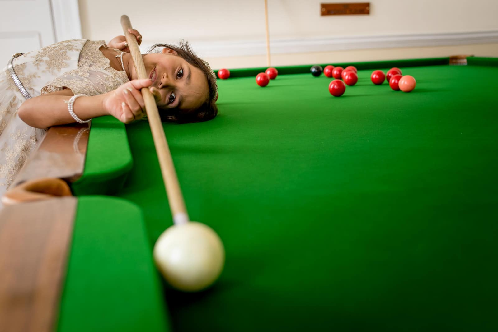 Flower girl playing pool at a Moor Park Golf Club wedding.