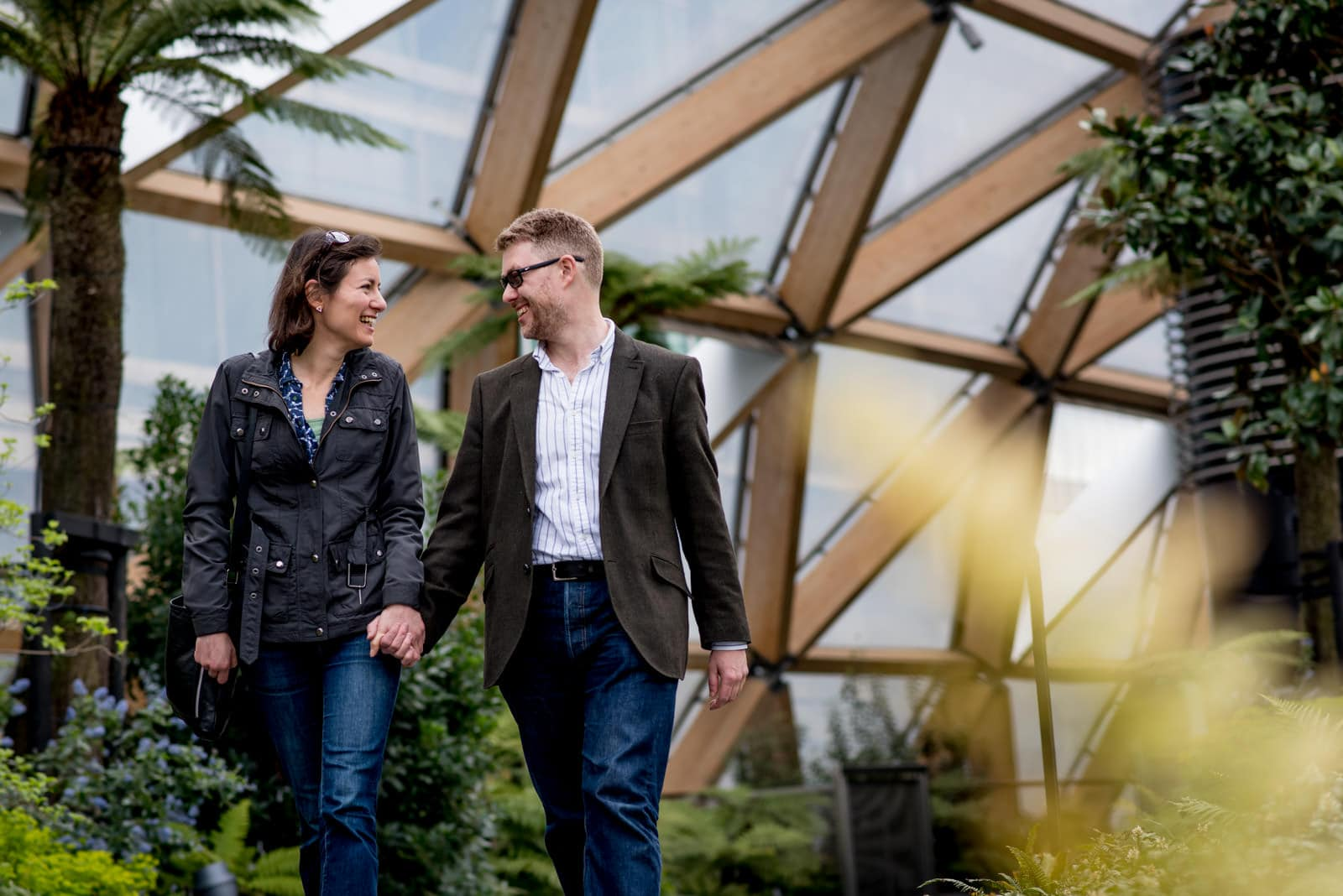Couple walking through Crossrail Place in Canary Wharf during their London engagement photos