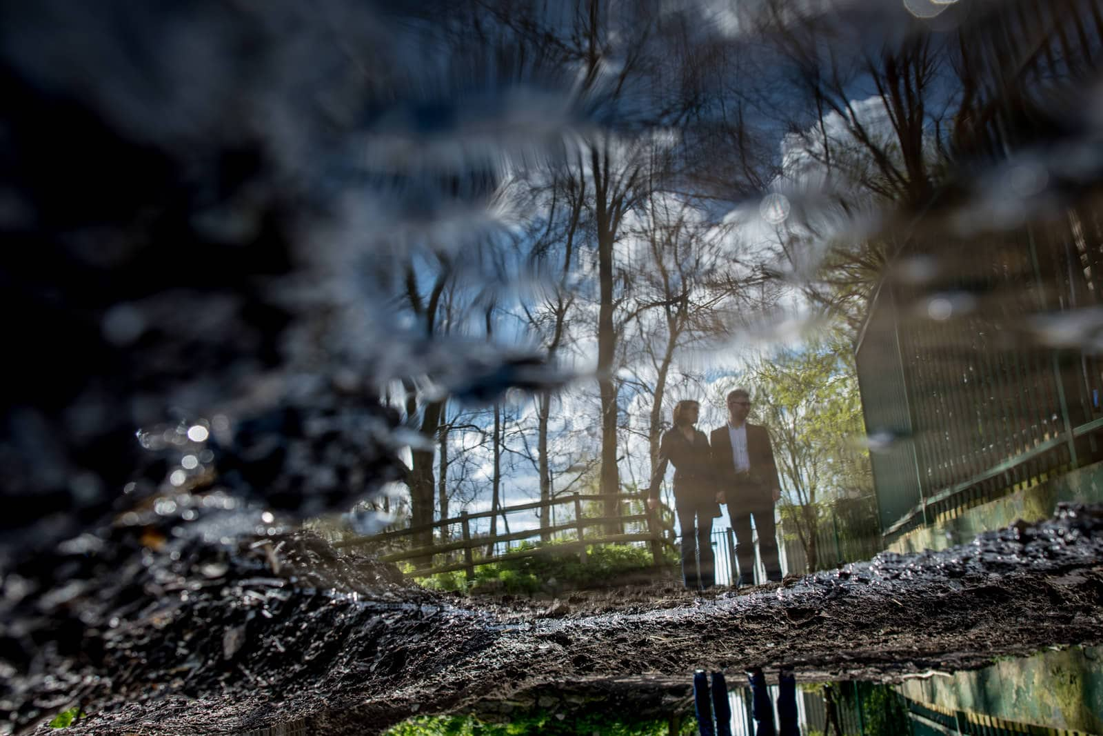 Reflection of couple in puddle at Mudchute Farm