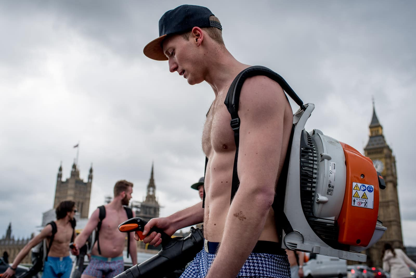A semi naked man with a leaf blower and skateboard racing on Westminster Bridge in front of Parliament in London