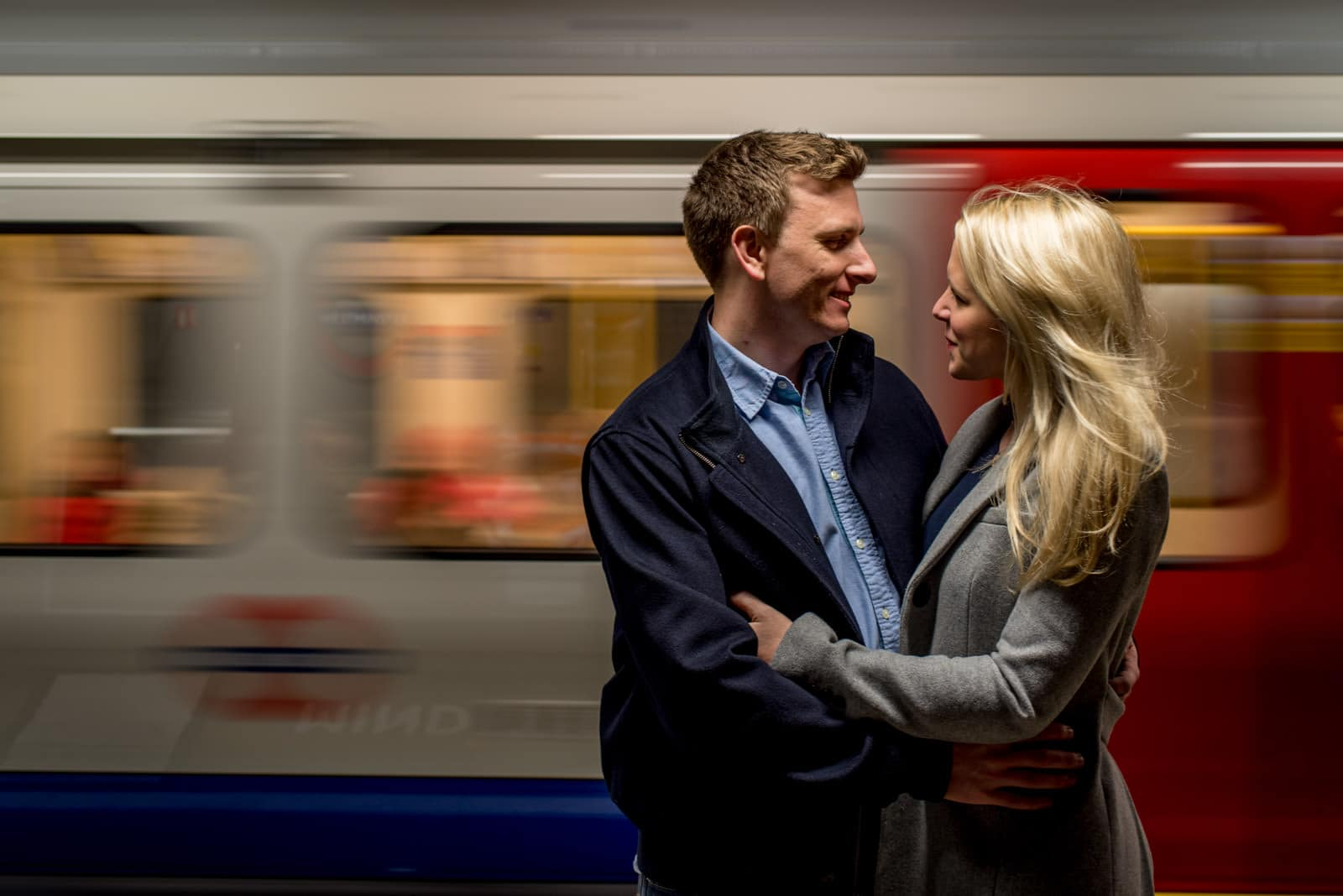 Couple engagement photo in front of moving train on London Underground