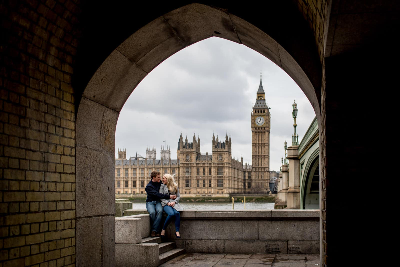 A creative photo of an engaged couple in front of the Houses of Parliament, Big Ben and Westminster Bridge on London's Southbank