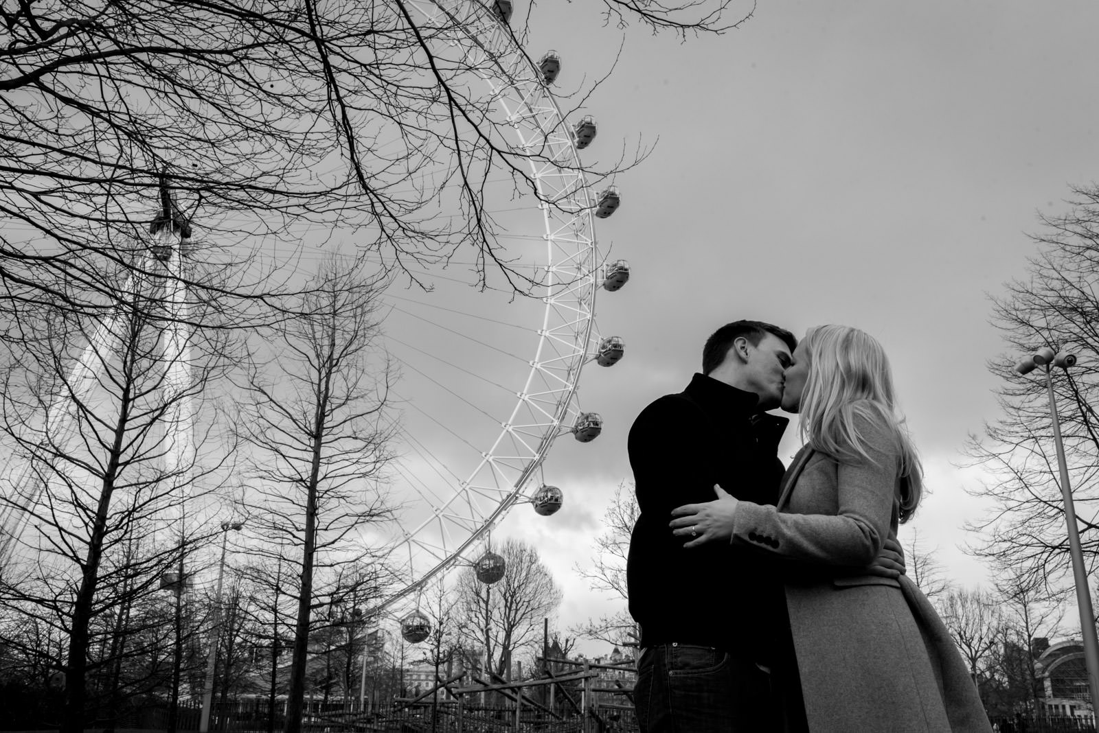 Black and white photo of couple kissing in front of the London Eye