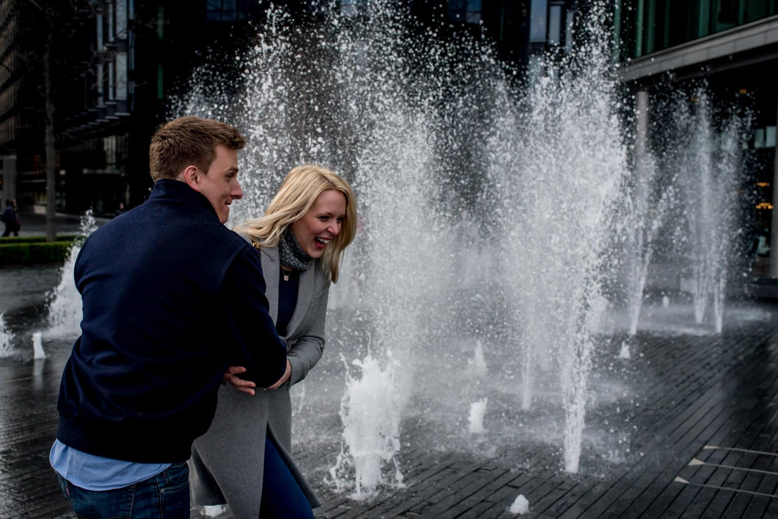 Couple playing in fountains on London's Southbank