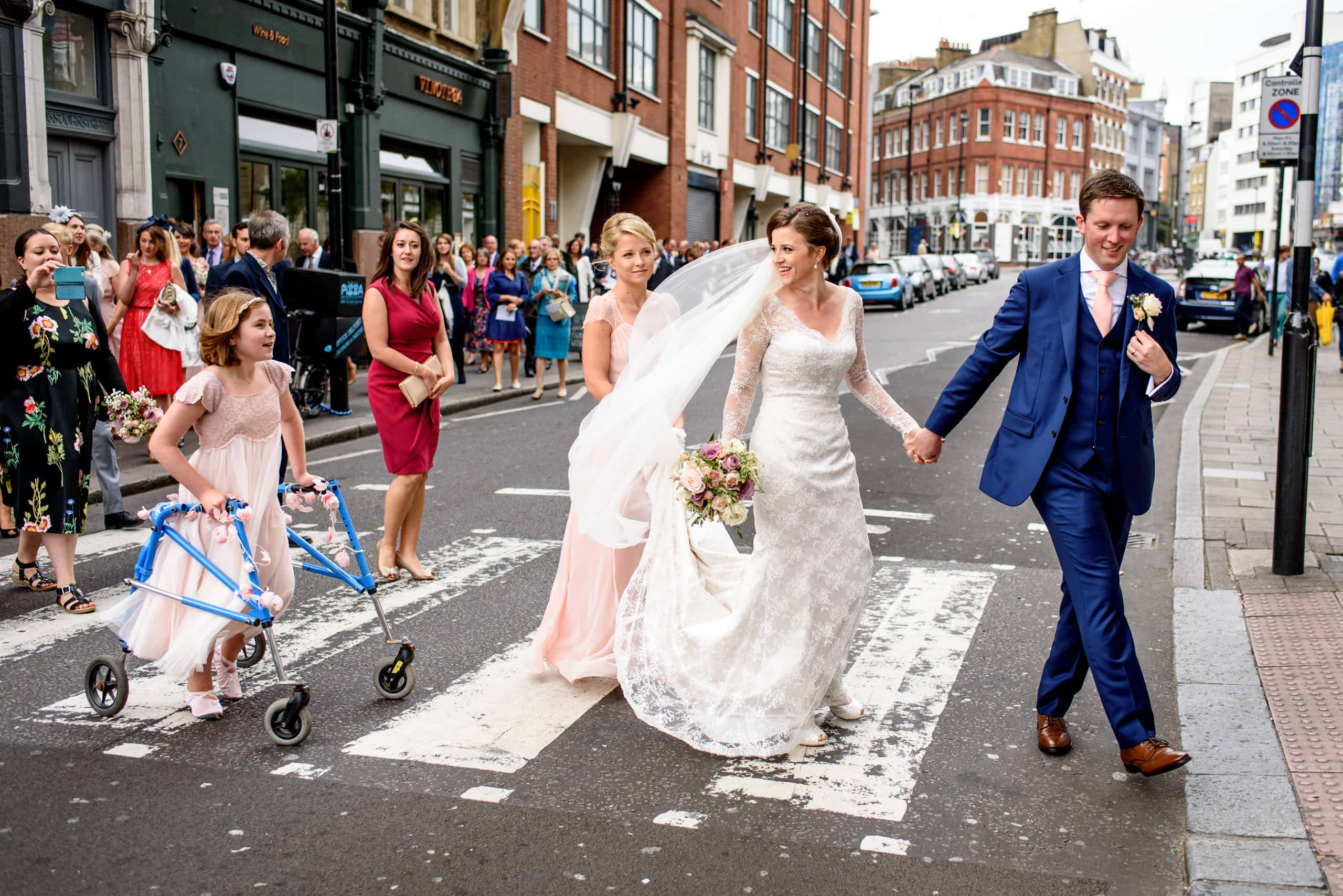 Bride and groom crossing road while leading their wedding parade in North London