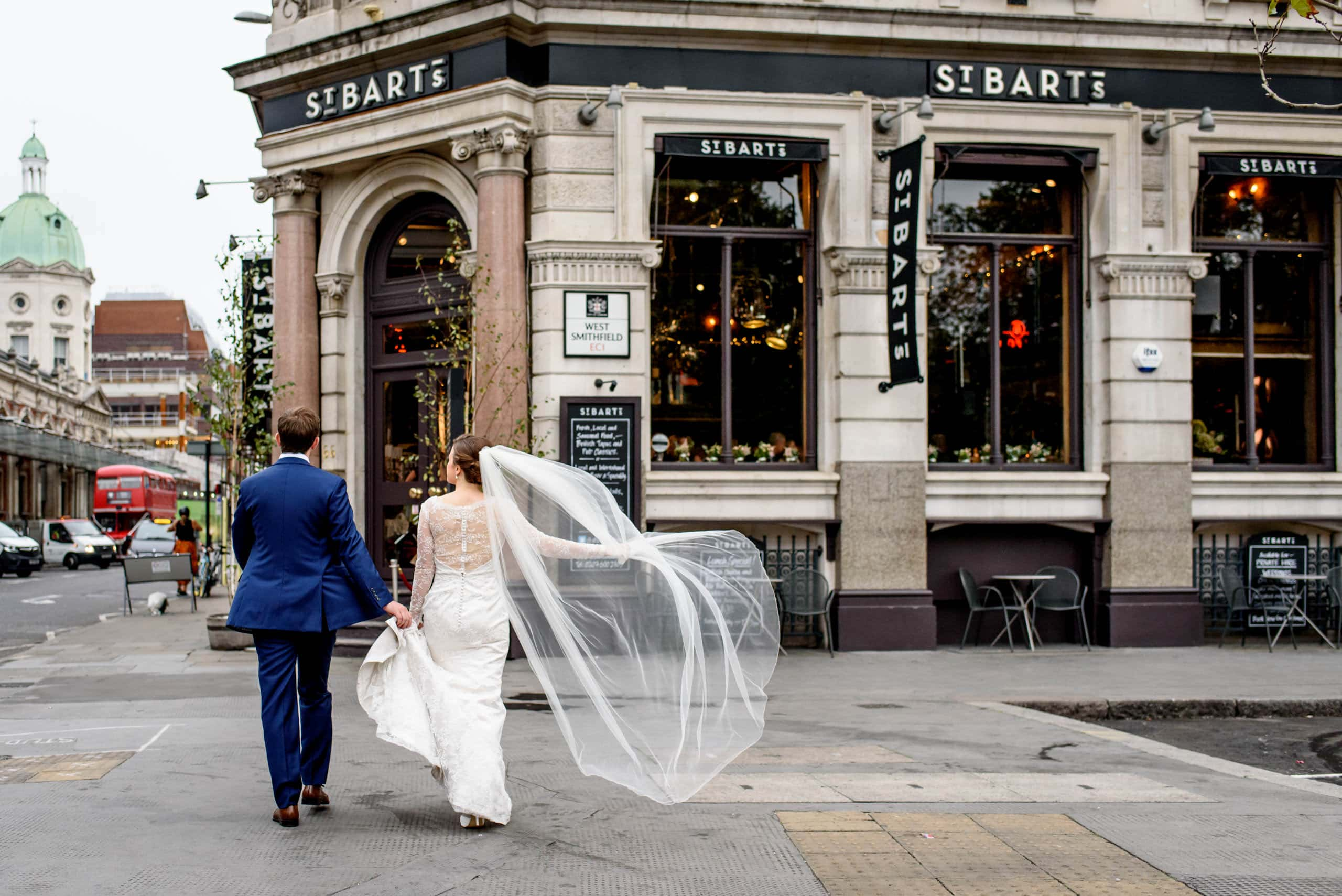 Groom and bride with her veil caught in the wind about to enter their St Bart's Brewery wedding celebrations in London
