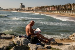 man reading newspaper on the beach in Barcelona for some Barcelona street photography