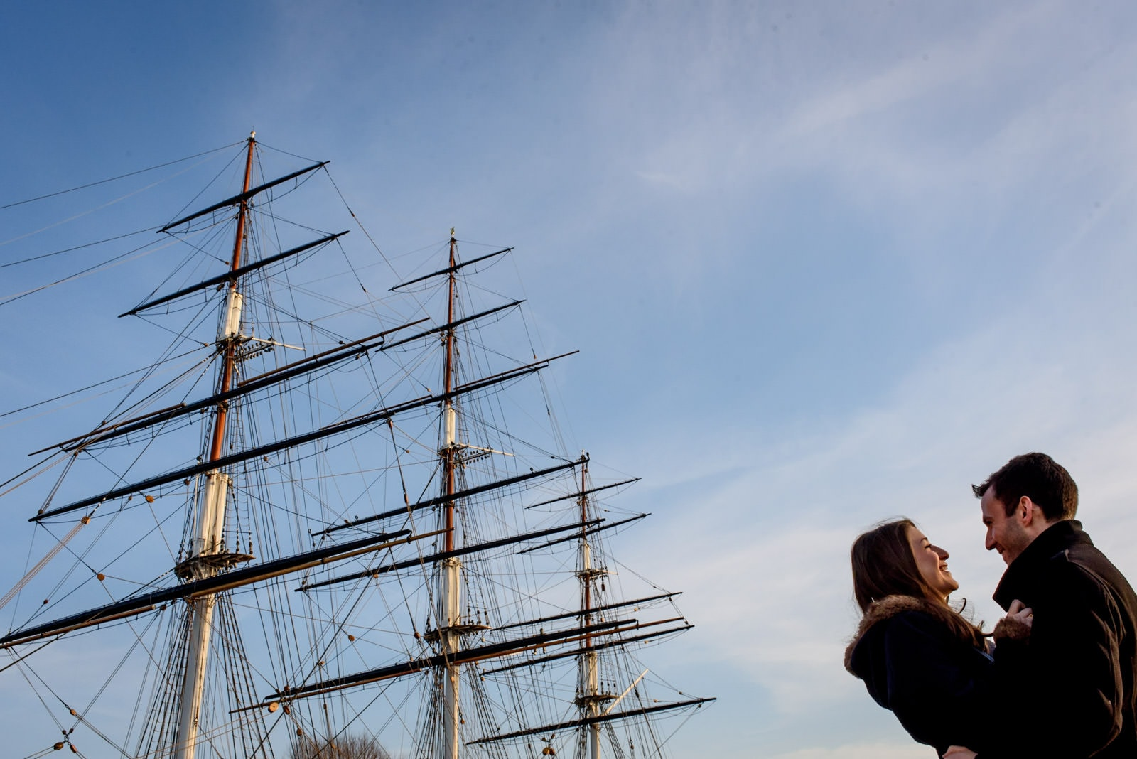 London engagement photos in front of the Cutty Sark against a blue sky