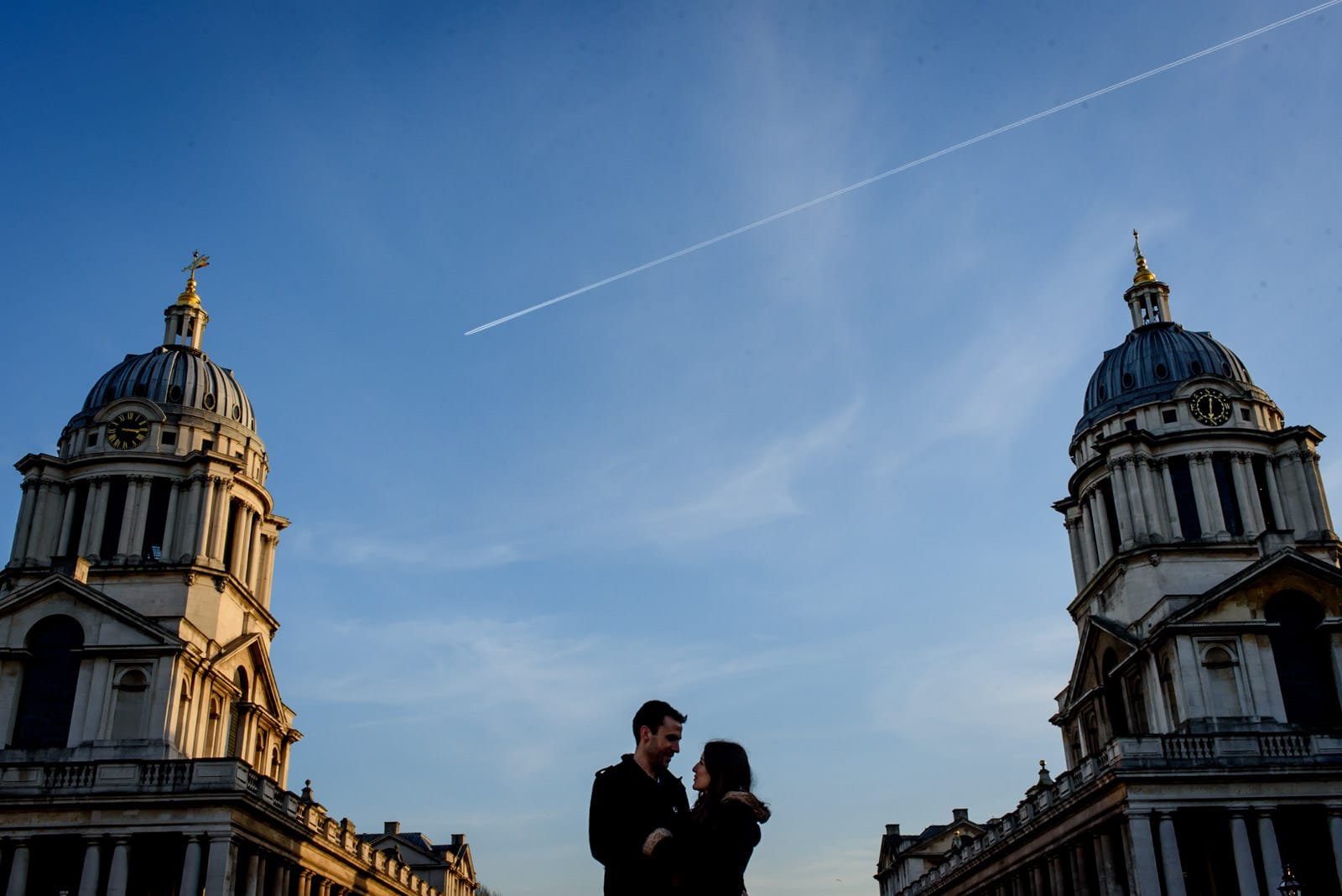 Engagement photos at Old Royal Navy College in Greenwich, couple silhouette against a blue sky