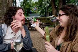 Photo of couple playing with bubbles during their London pub engagement shoot