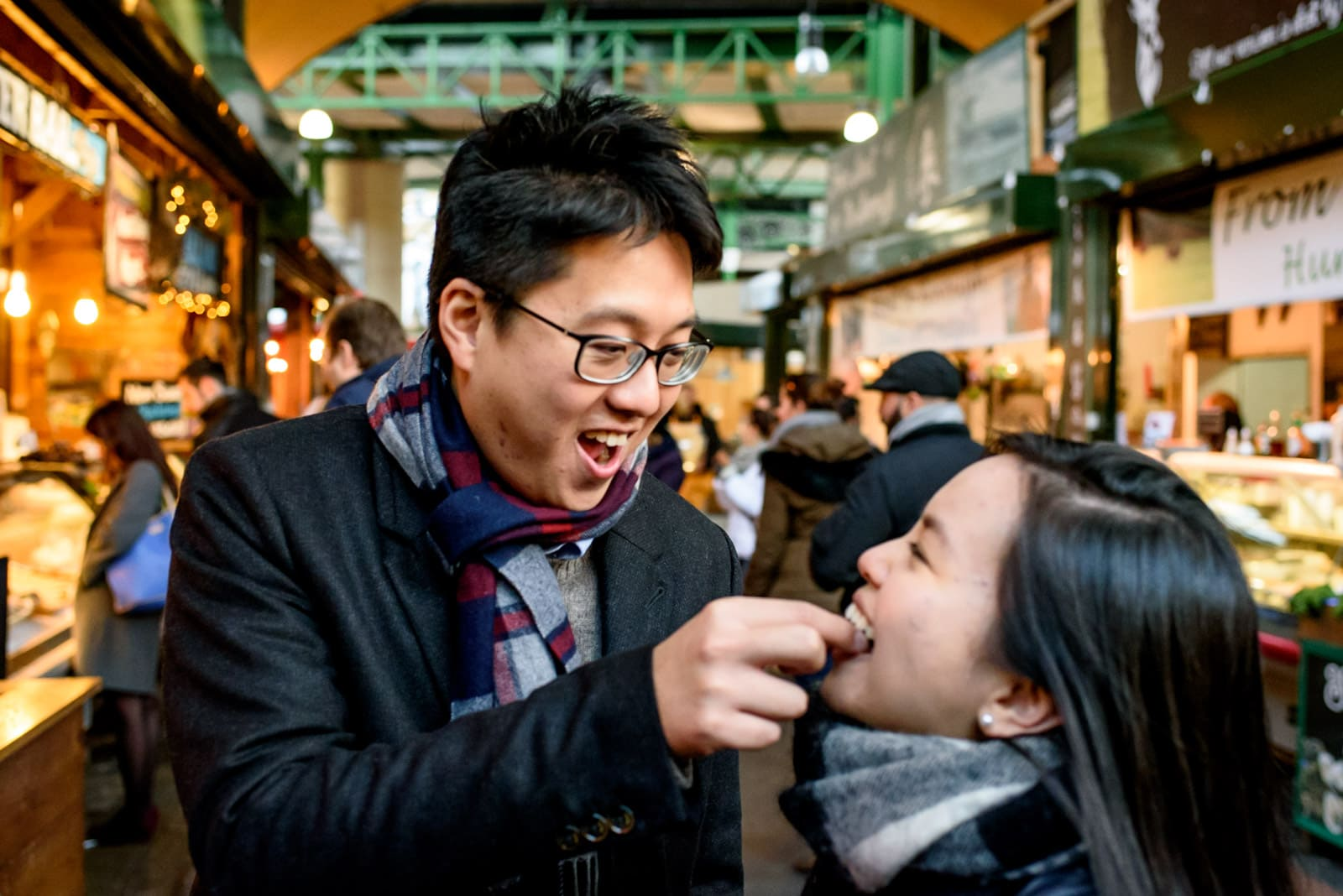 Photo of couple eating during their Borough Market engagement shoot in London