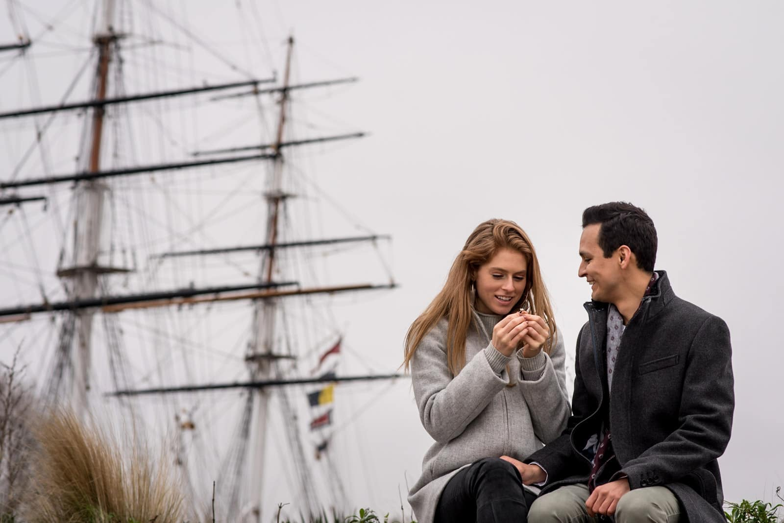 Photo of fiance admiring her ring after proposal next to Cutty Sark in Greenwich, London