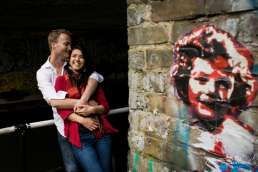 Photo of couple hugging during their London engagement session with graffiti