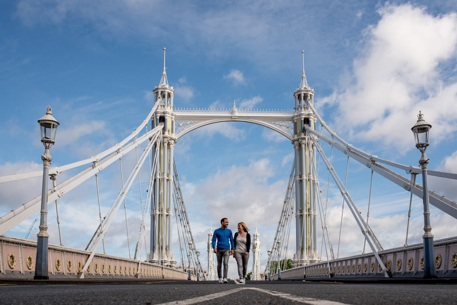 Photo of couple walking with blue sky for their Albert Bridge engagement shoot in London wearing summer clothes