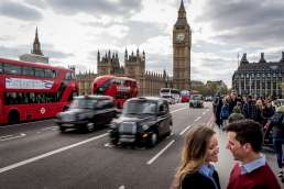 Photo of couple in front of Red double decker buses and black taxis during their westminster bridge engagement shoot in London