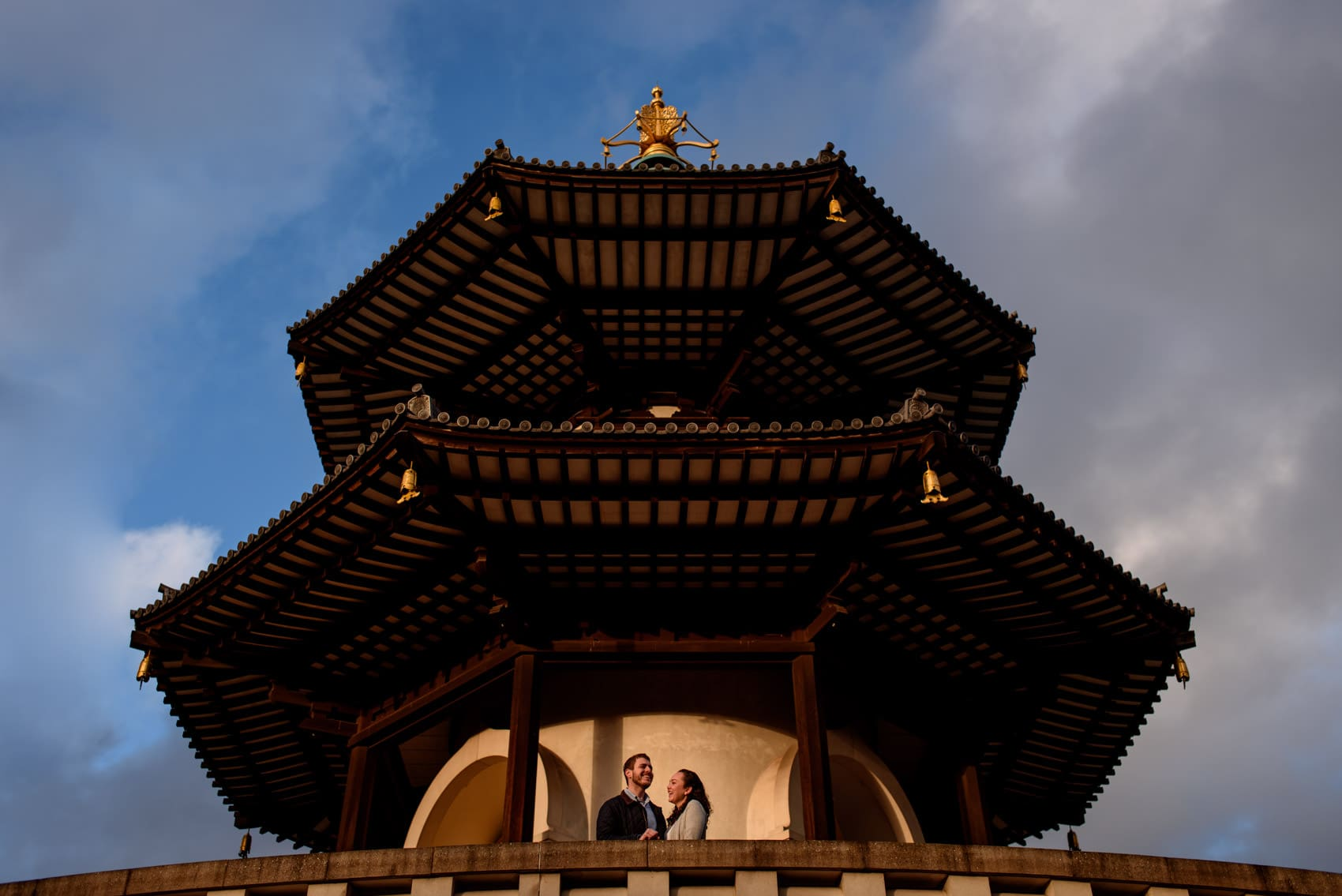 Photo of couple during their outside the Battersea Park peace pagoda at sunset during their London engagement photography session