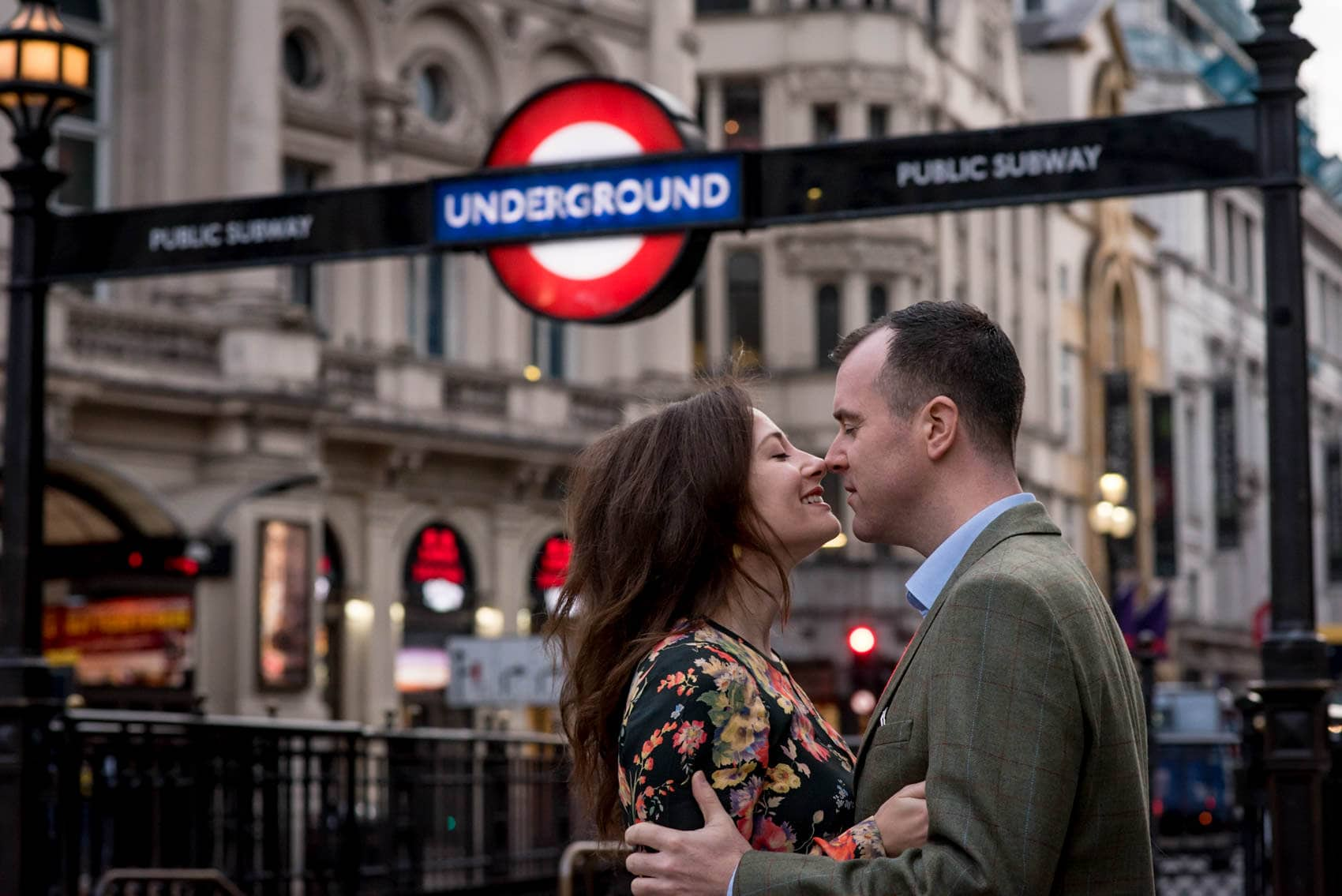 Photo of couple kissing outside the London Underground during their Piccadilly Circus engagement photo shoot