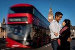 Photo of a couple during their london engagement photo shoot outside of Big Ben with a red double decker bus