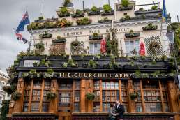 Photo of couple outside the Churchill Arms pub in Nottinghill during their London engagement photography session