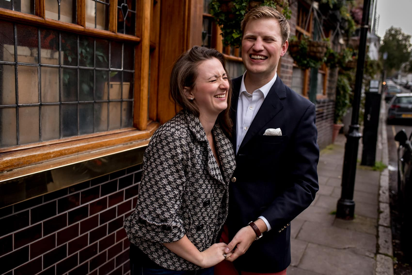 Photo of couple laughing outside a London pub during their Nottinghill engagement photo shoot
