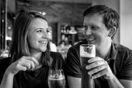Photo of couple drinking pints during their London pub engagement photo shoot