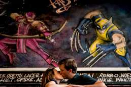 Photo of couple kissing during their Vaults London engagement shoot with graffiti of Wolverine and Hawk Eye