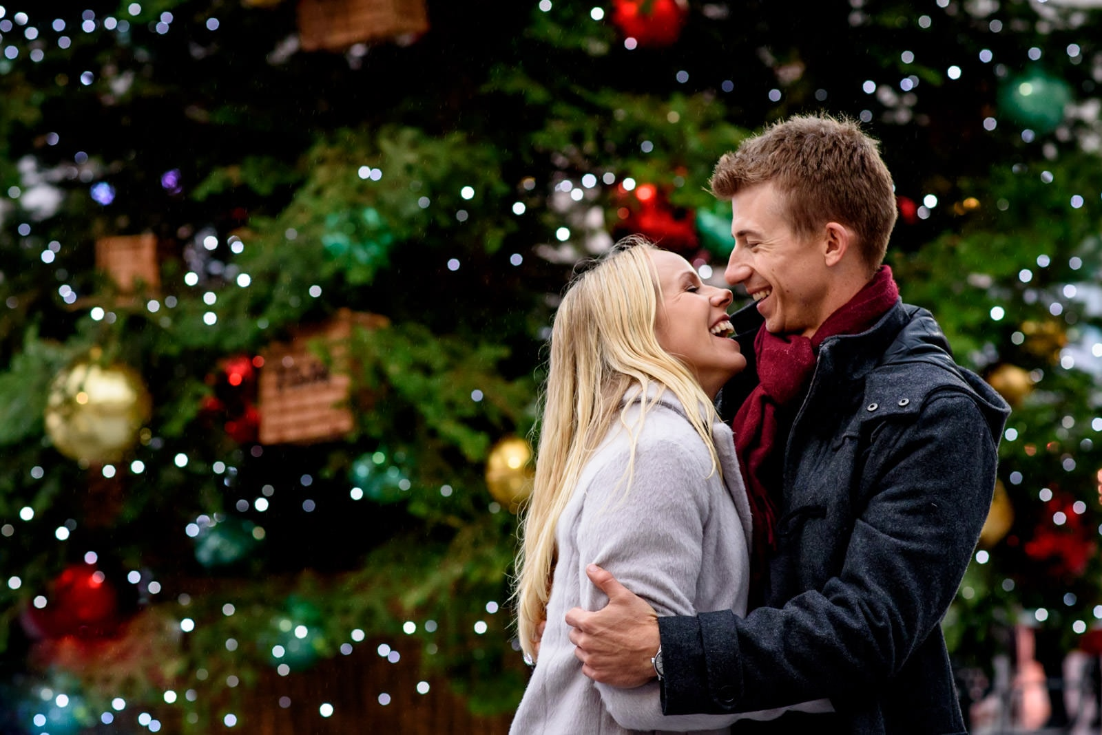 Photo of couple in front of a Christmas tree during their London winter engagement shoot