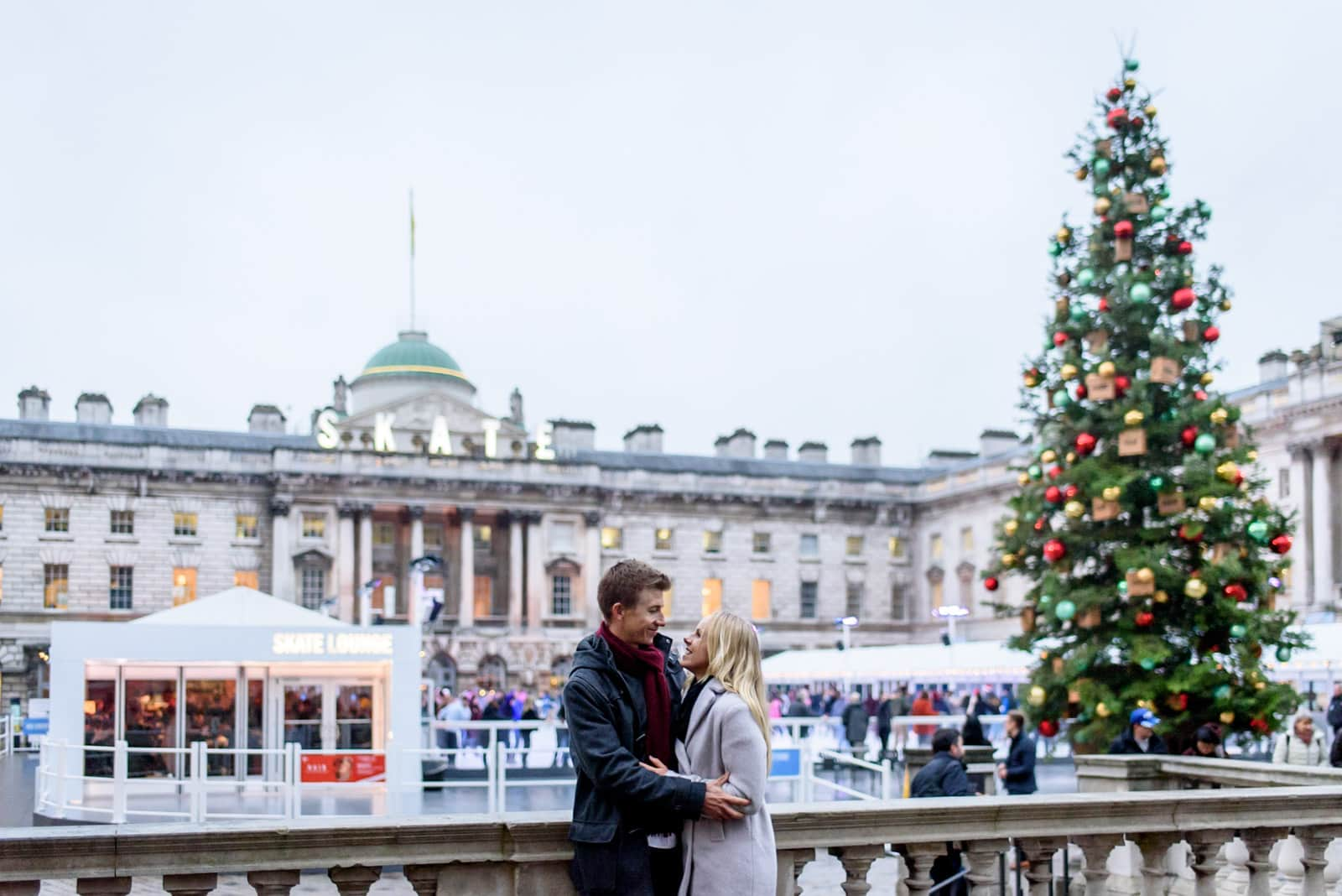 Photo of couple during their Somerset house engagement photo session with a Christmas tree in London