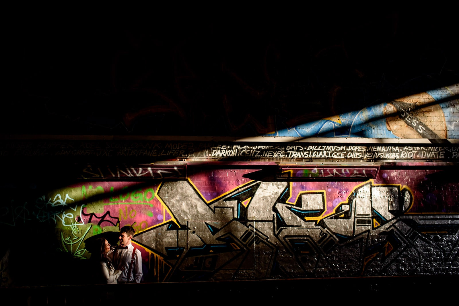 Photo of couple in front of graffiti during their Leake street engagement photography shoot, aka the vaults