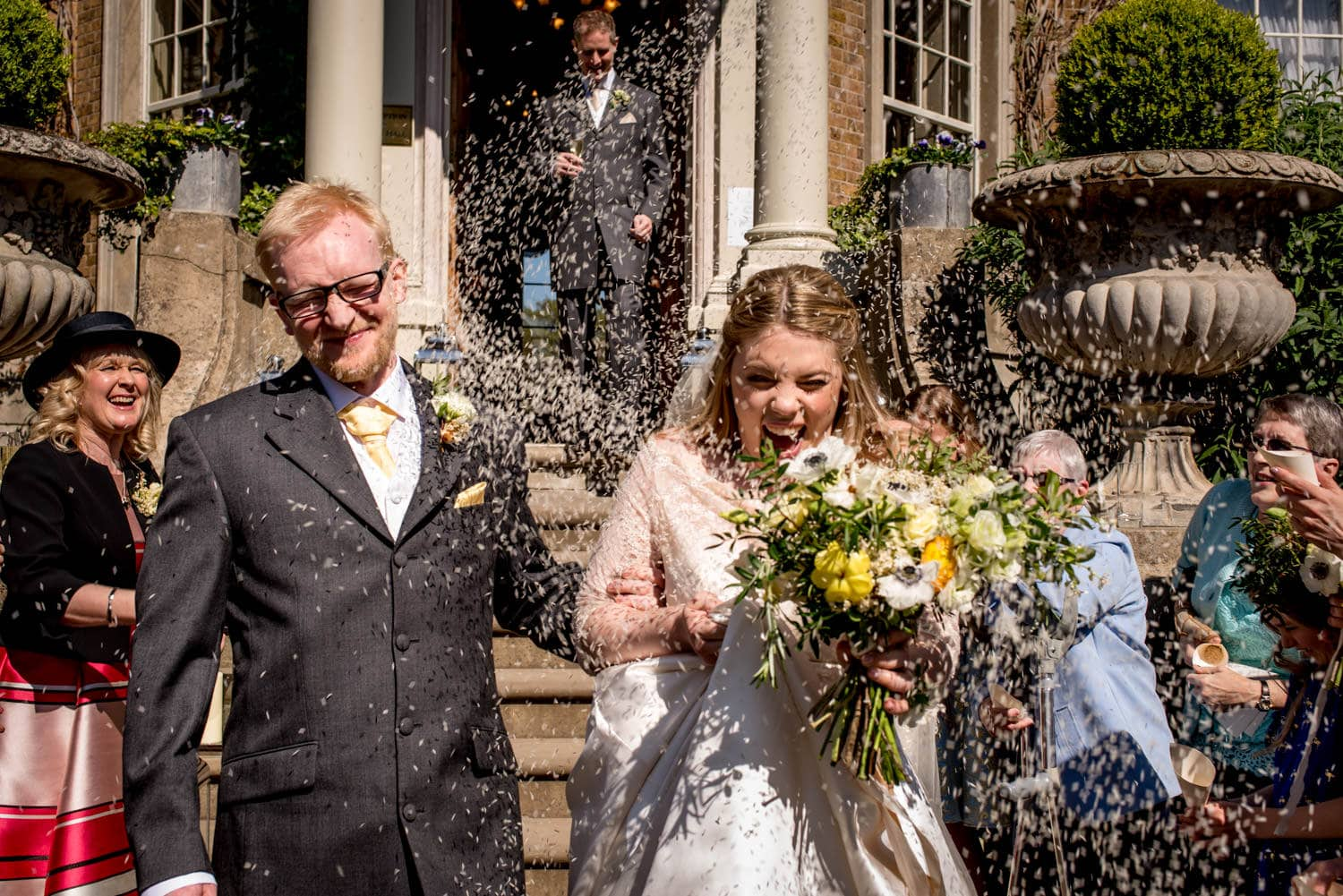 rice confetti being thrown at the couple at their wedding at Hampton Court House, London.