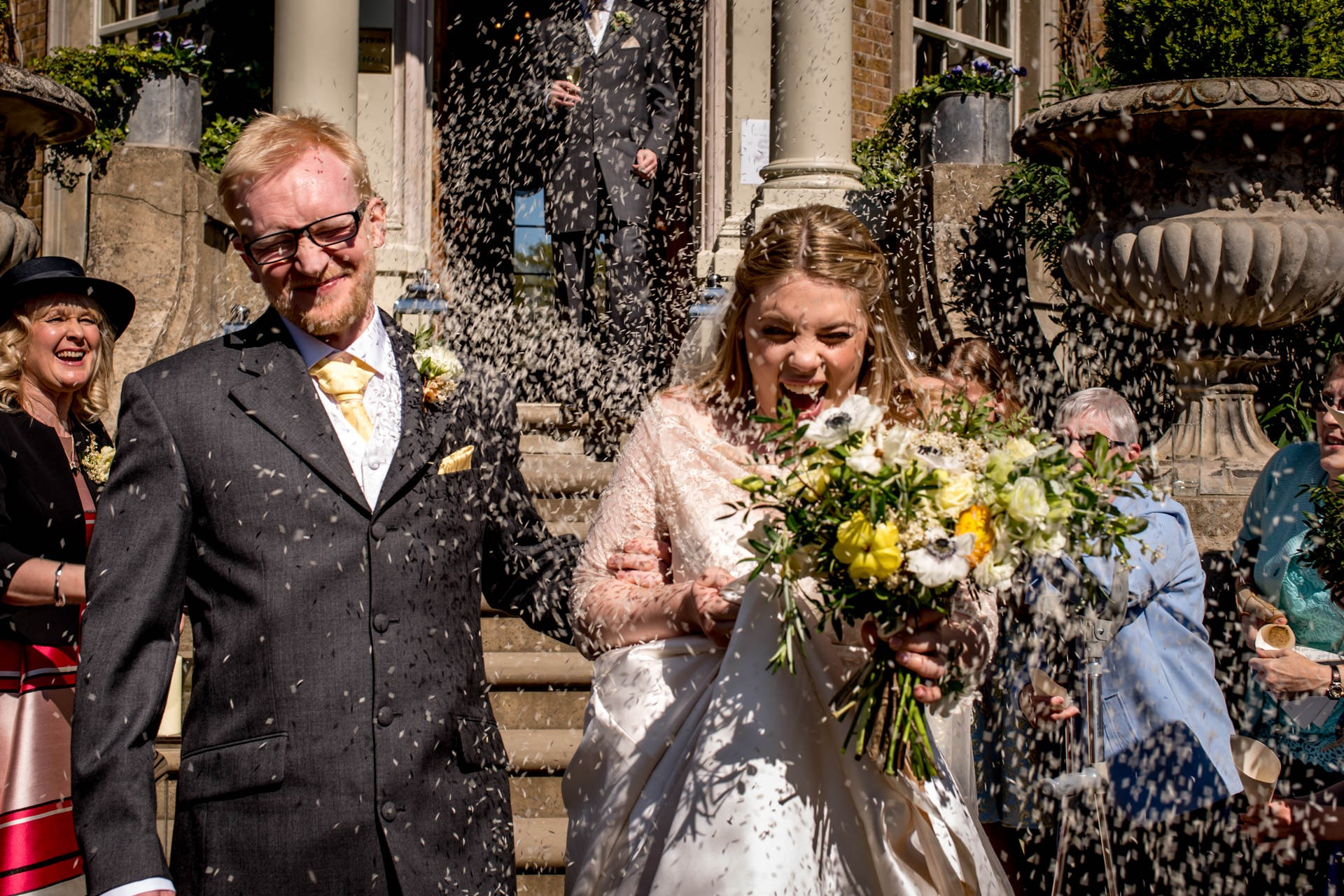 Rice confetti being thrown at bride and groom at their Hampton Court House spring wedding