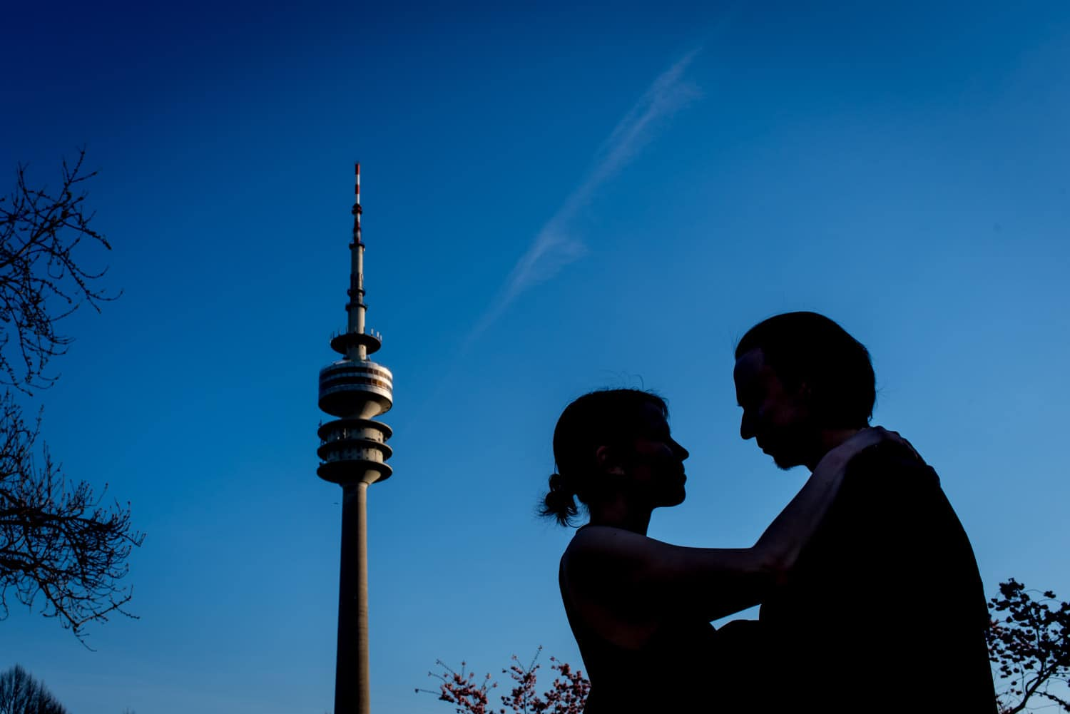couple photo in front of Munich Olympic Stadium tower with blue sky
