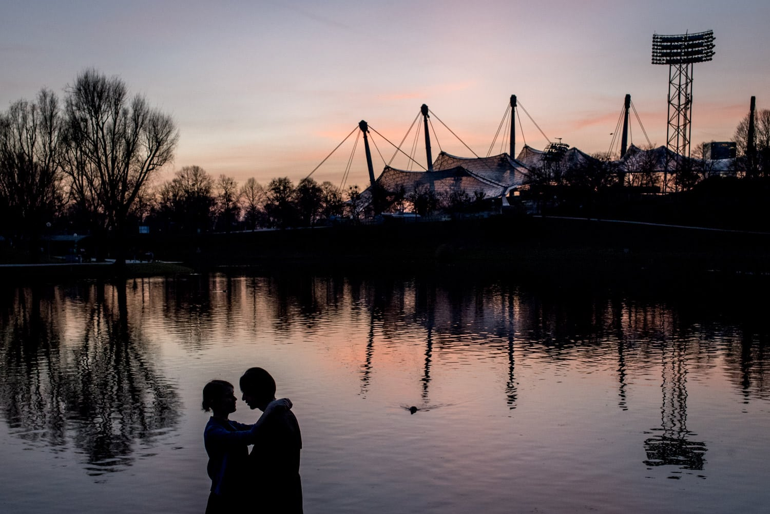 sunset photo with couple in front of lake and stadium at the Munich Olympic Park
