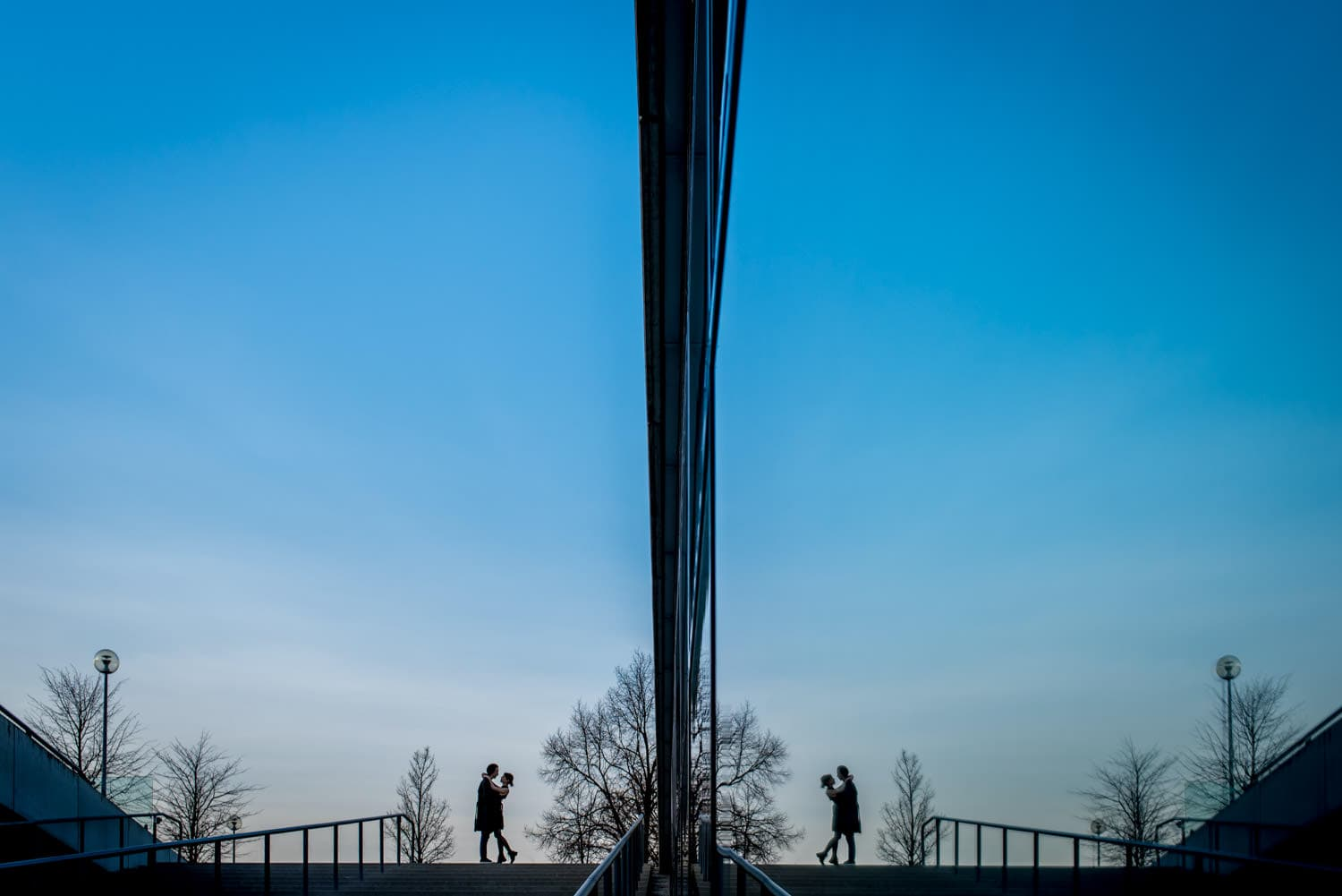 couple in glass reflection with blue sky
