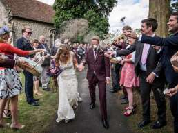 guests throwing lavender wedding confetti at bride and groom