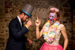 Bride and groom wearing fancy dress and UV paint on the dancefloor