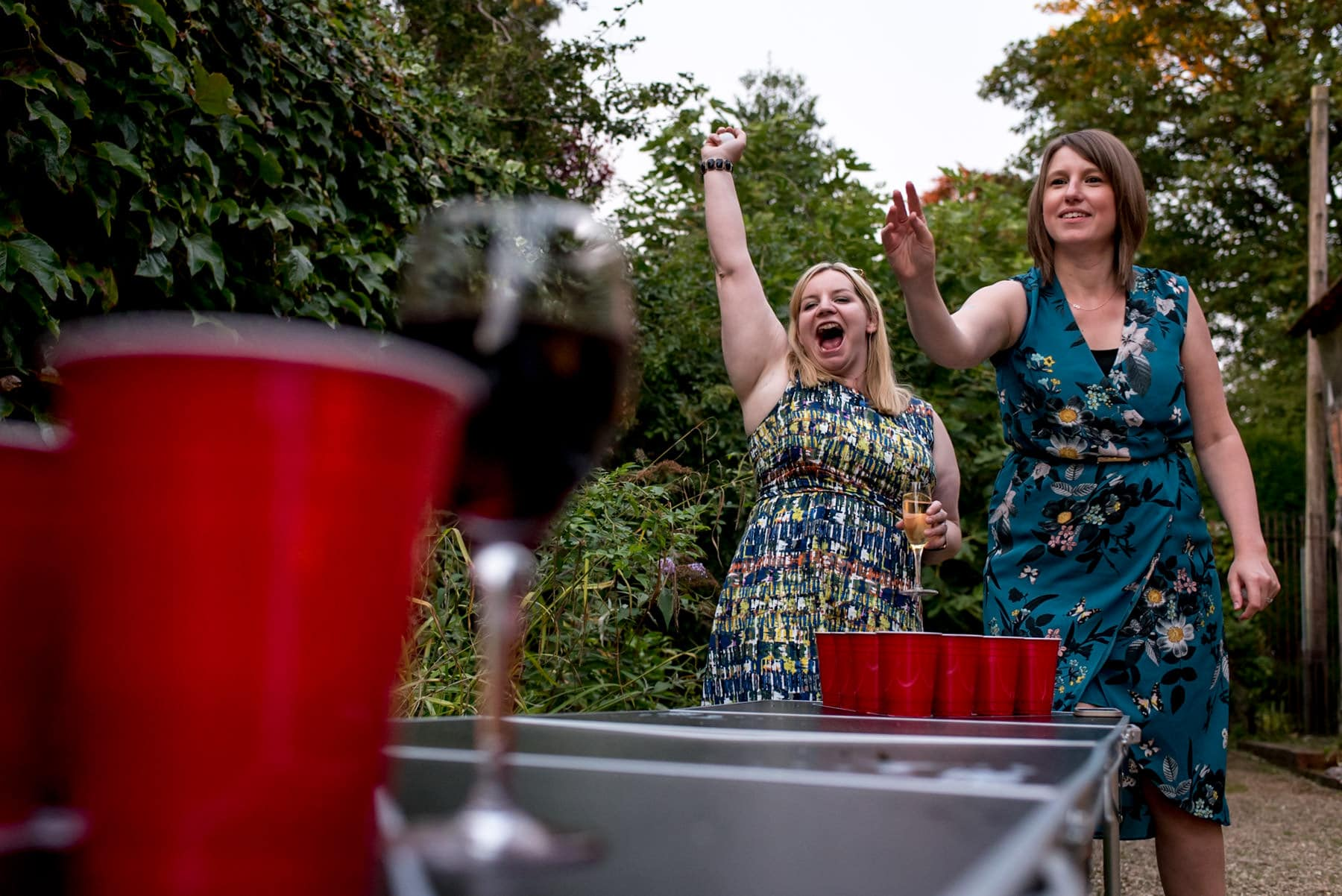 two girls playing beer pong and cheering at a wedding