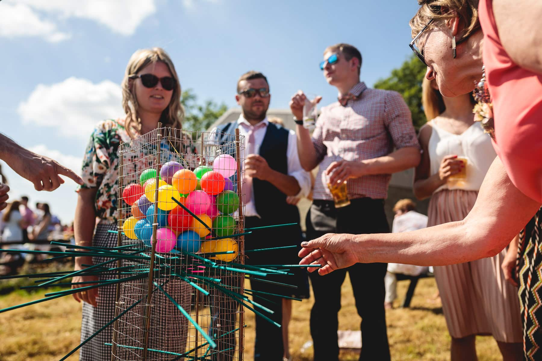 wedding guests playing giant kerplunk outside in the sun