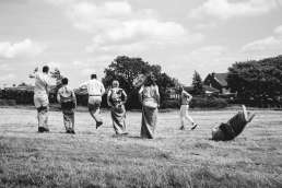 wedding guests doing a sack race in a field with one falling over