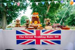 A table of cakes with a poster that reads 'The Great Wedding Bake Off'