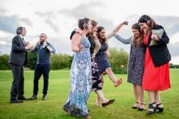 A group of wedding guests dancing outside in a field with silent disco headphones