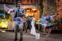 wedding guests having fun with a giant bubble maker