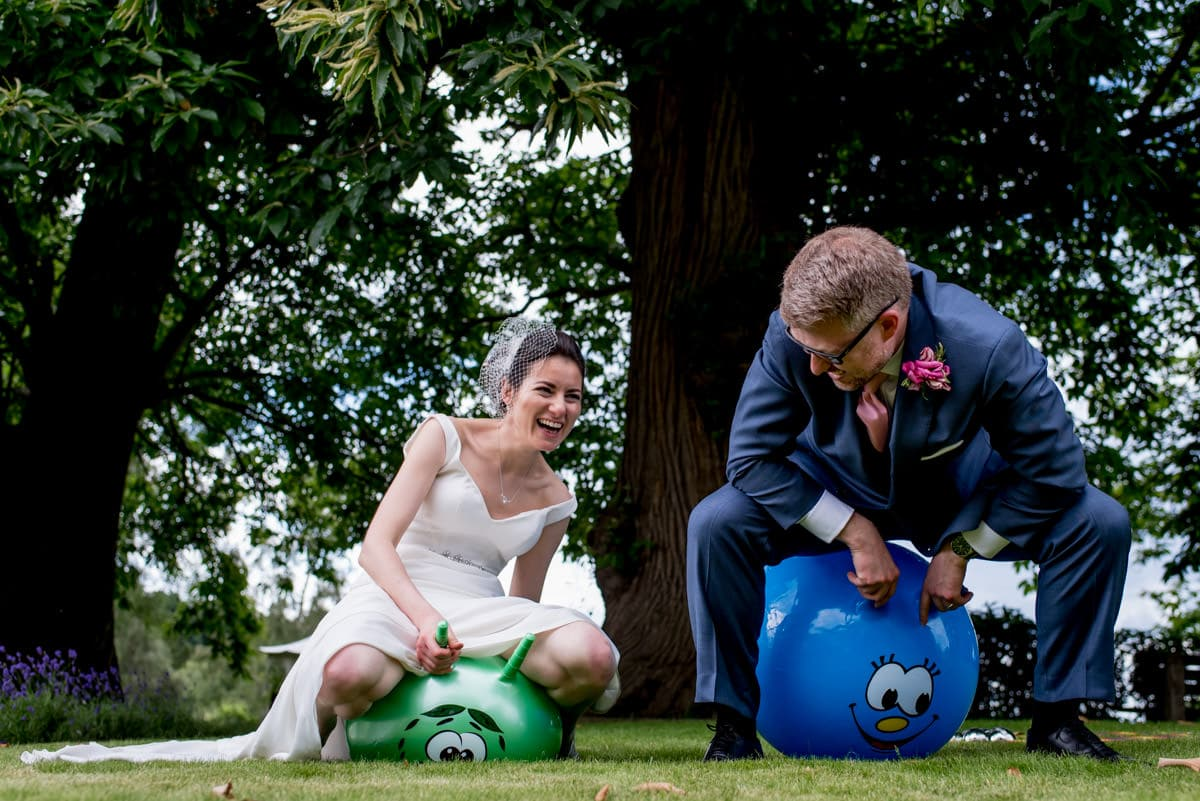 bride and groom jumping around on space hoppers at their wedding