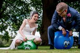 bride and groom bouncing on space hoppers as their wedding entertainment