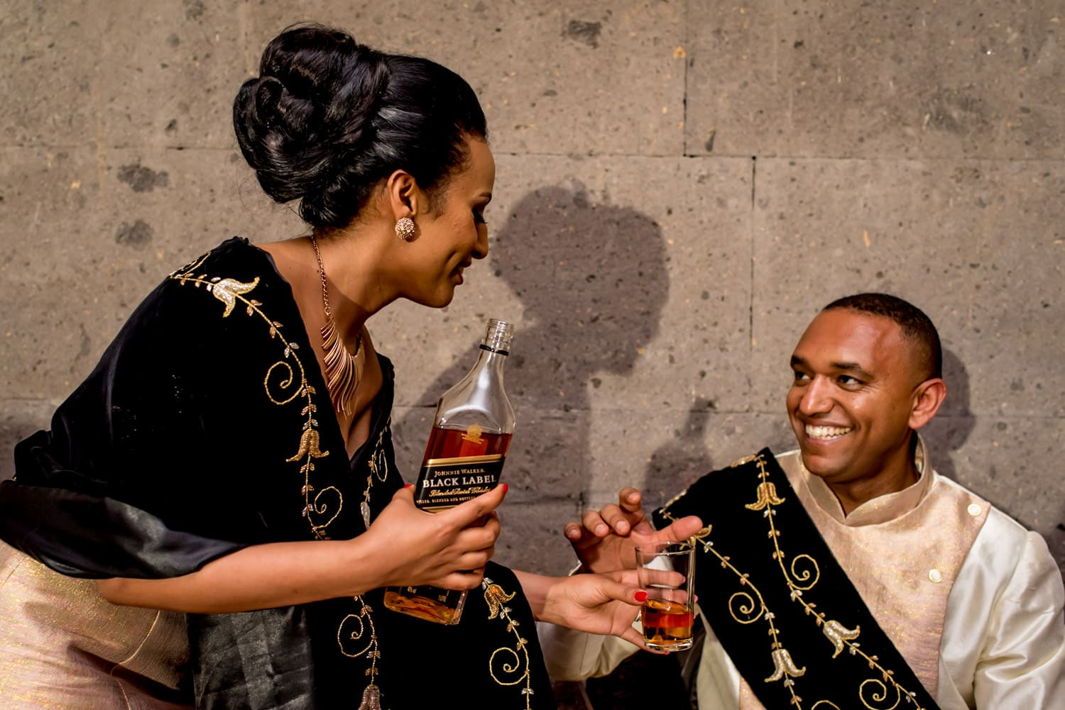 Ethiopian bride pouring groom a glass of johnny walker black label whiskey