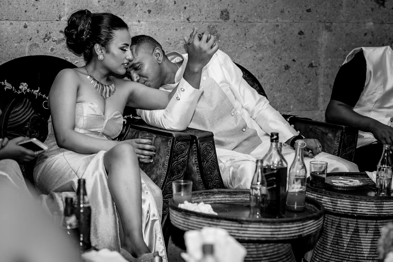 Ethiopian wedding photography of groom kissing arm of the bride
