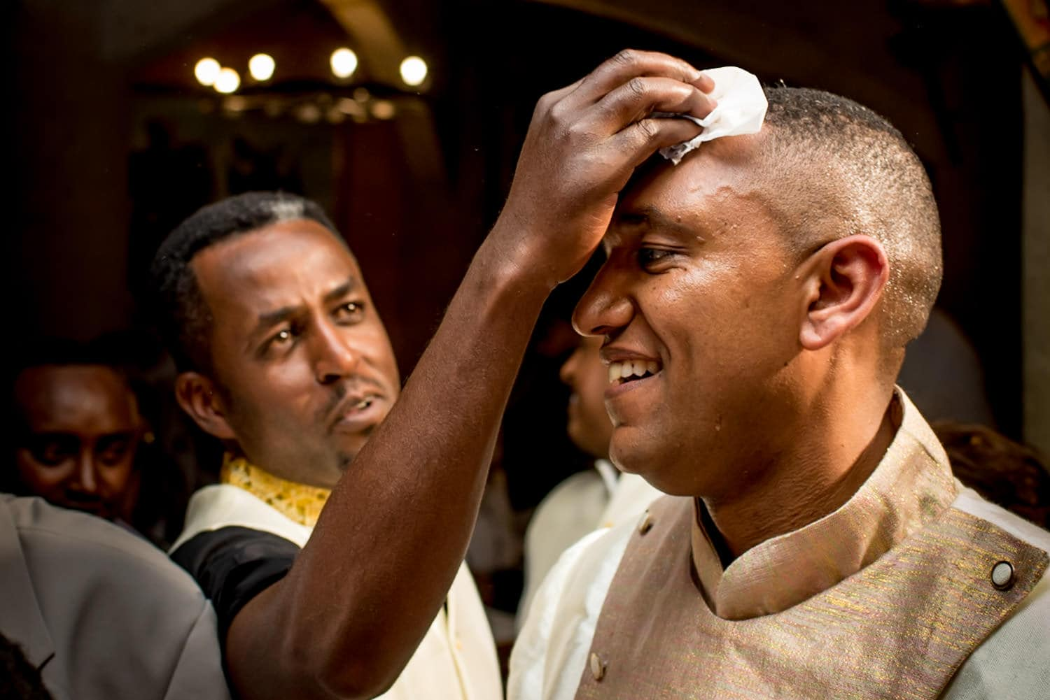 groomsman dabbing sweat off the grooms head at this Ethiopian Wedding