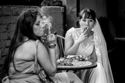 black and white photo of bride smoking with her bridesmaid