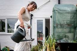 bride watering her plants with a watering can in her wedding dress