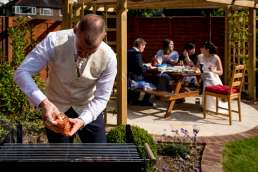 groom cooking a BBQ for his guests at his intimate garden wedding in London